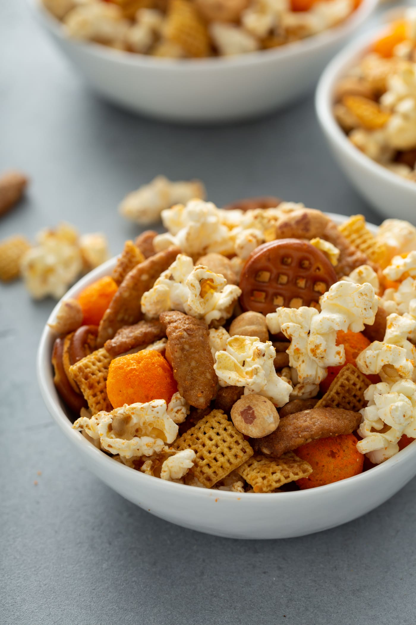 A bowl of savory March madness snack mix. It has popcorn, peanuts, chex, pretzels, and sesame sticks. There are other bowls of mix in the background.
