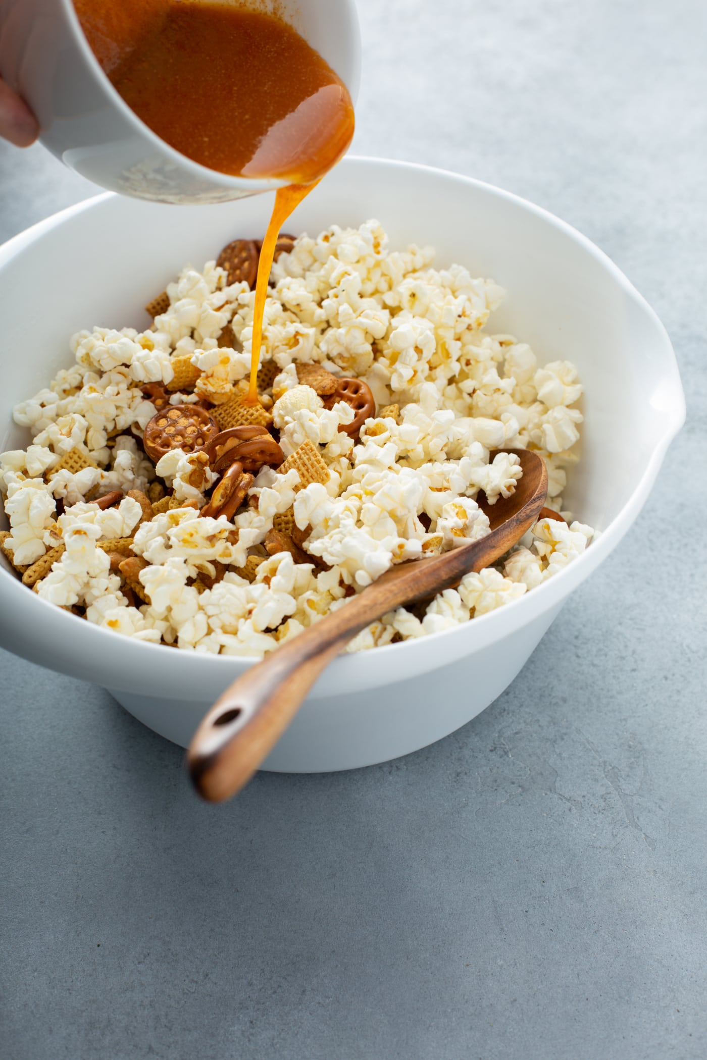 A bowl of popcorn other ingredients for 5 minute savory snack mix. Melted butter and spices are being poured over the popcorn.