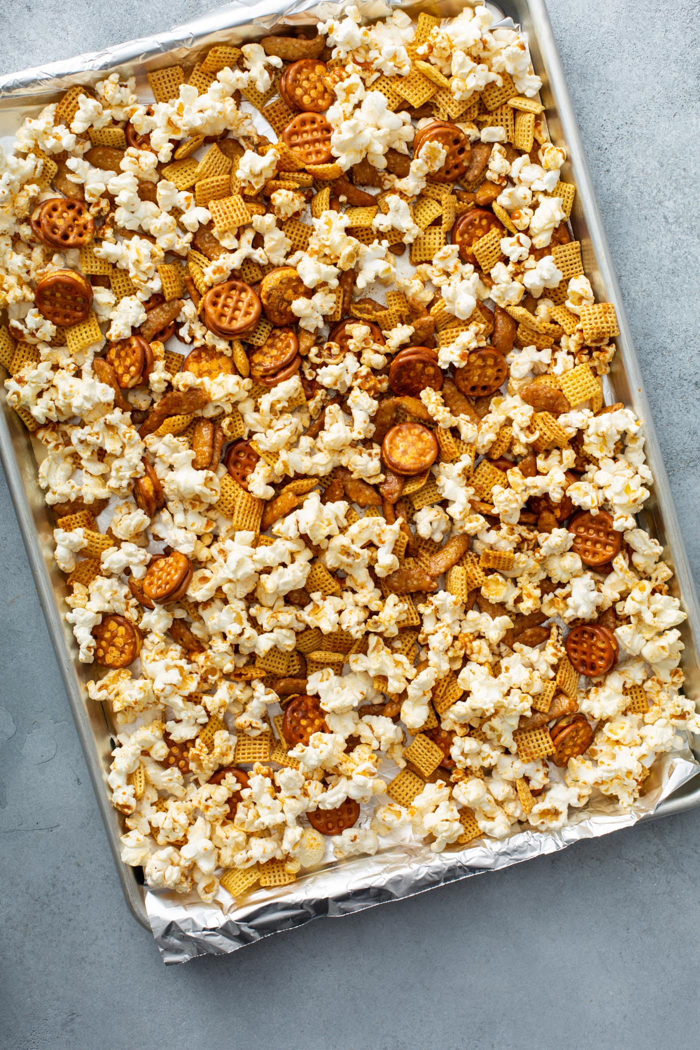 A baking sheet filled with popcorn, chex, pretzels, and sesame sticks.