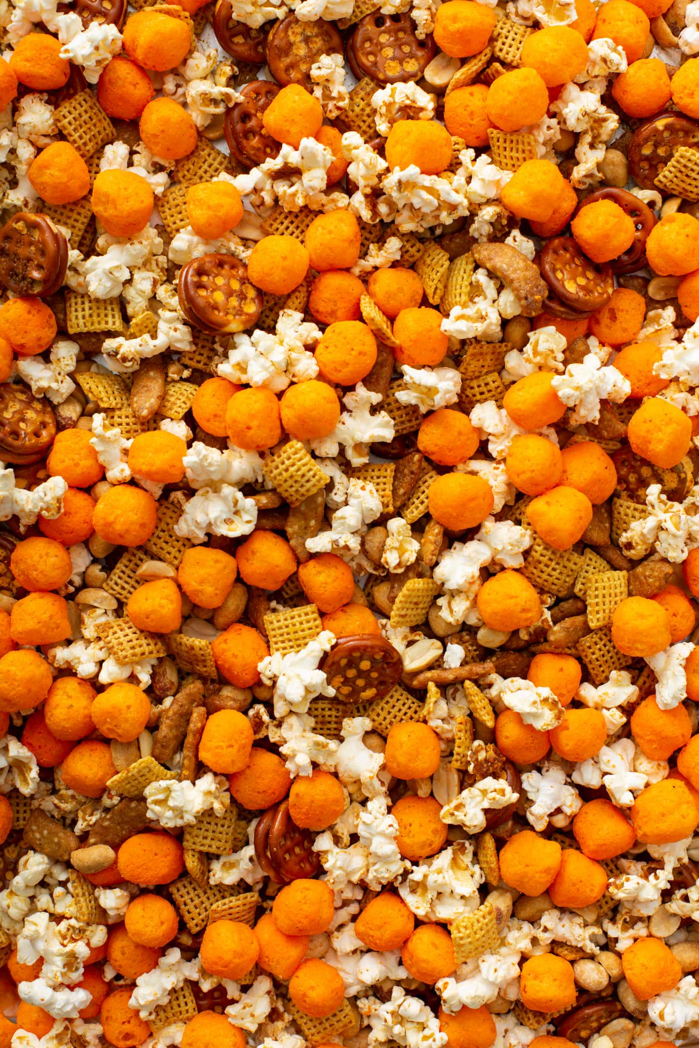 A close up of March madness snack mix. There are cheese balls, pretzels, sesame sticks, chex and popcorn mixed together in butter and spices.