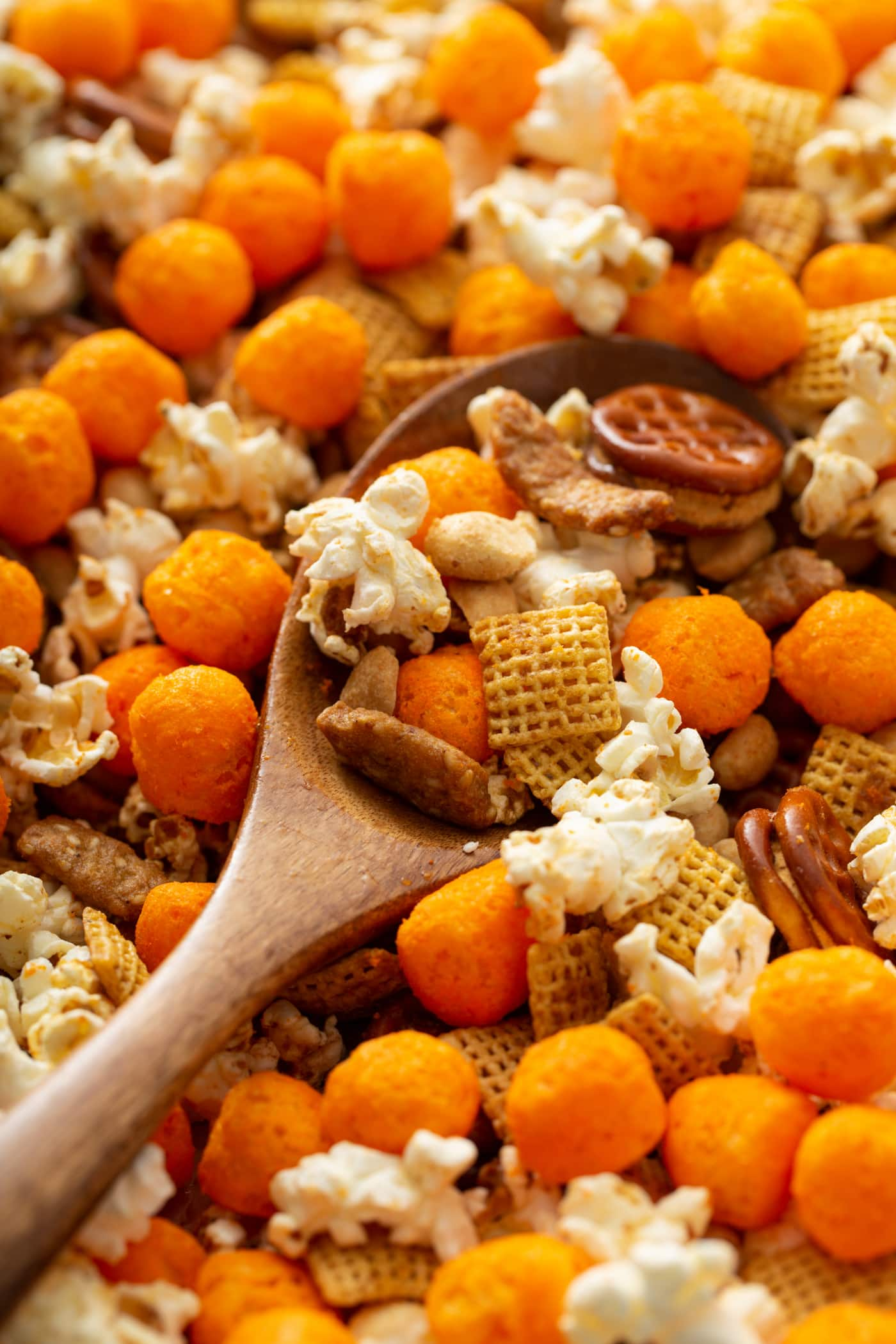 A wooden spoon dipping a big scoop of March madness snack mix. There is popcorn, cheese balls, chex and pretzels in the mix.