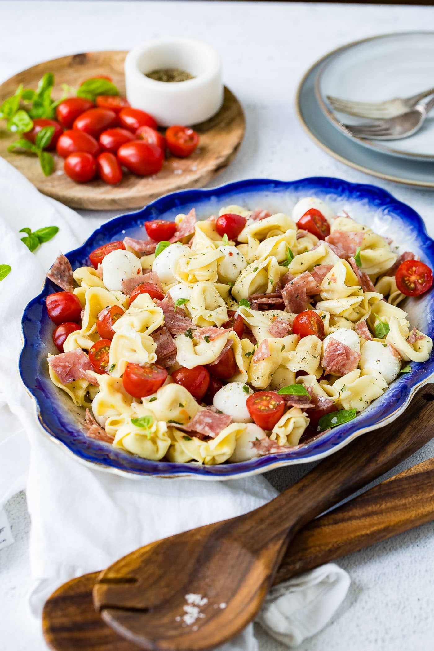 A blue edged serving dish of 5 minuted Italian salami tortellini salad. There are chunks of salami and slices of tomato in the tortellini. There are also mozzarella balls in the salad. A cutting board with grape tomatoes is in the background.