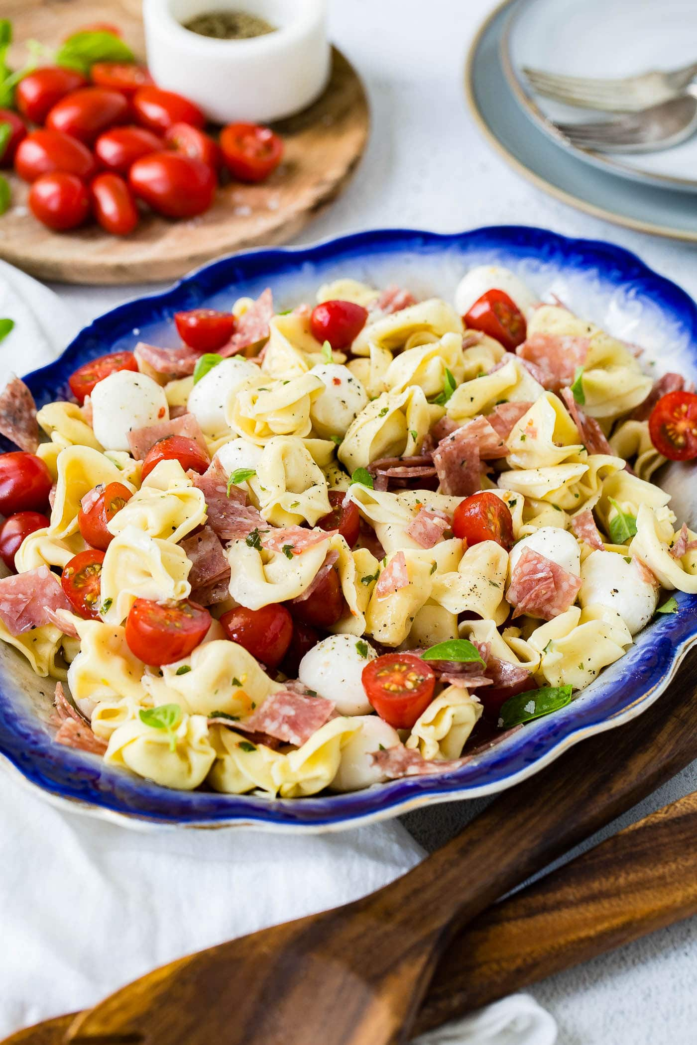 A blue edged serving dish of 5 minute salami tortellini salad. There are chunks of salami, sliced grape tomatoes, and mozzarella balls mixed in with the tortellini. A wooden cutting board with grape tomatoes is in the background.
