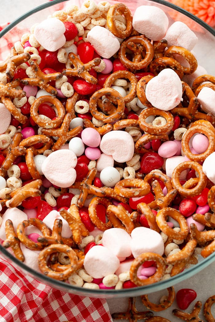 A close up photo of a Valentine's snack mix including frosted cheerios, Valentine's caramel M&Ms, X and O shaped pretzels, pink heart marshmallows, Valentine's colored plain M&Ms, and heart shaped Starburst jelly beans.