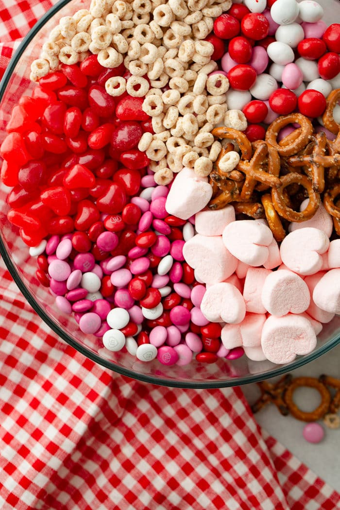 A photo of a large glass bowl full of frosted cheerios, Valentine's caramel M&Ms, X and O shaped pretzels, pink heart marshmallows, Valentine's colored plain M&Ms, and heart shaped Starburst jelly beans with a red and white checkered napkinon the side.