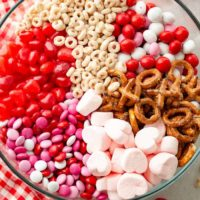 A photo of a large glass bowl full of frosted cheerios, Valentine's caramel M&Ms, X and O shaped pretzels, pink heart marshmallows, Valentine's colored plain M&Ms, and heart shaped Starburst jelly beans.
