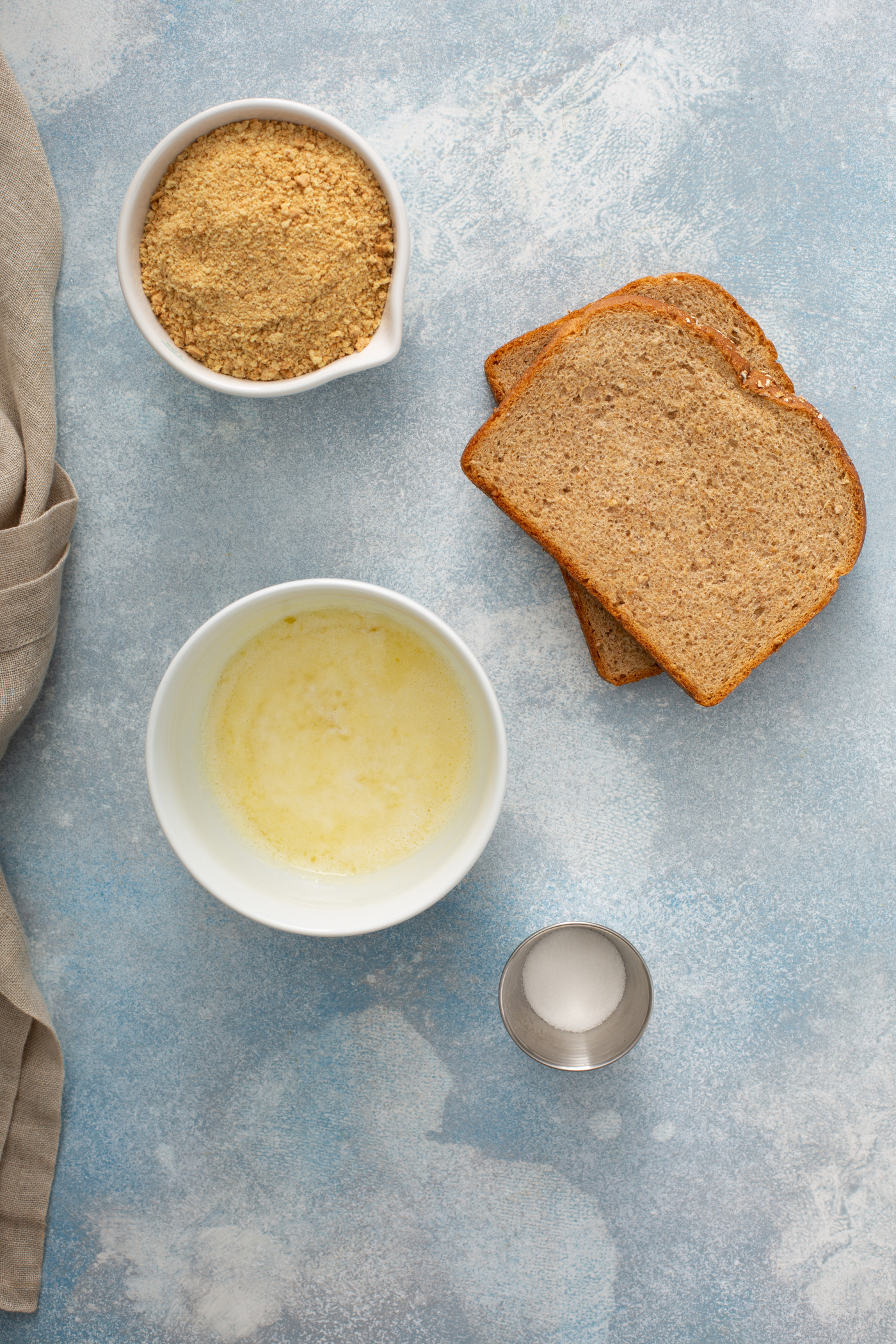Two slices of brown bread, containers of melted butter, salt, cinnamon and sugar all sitting on a table top.