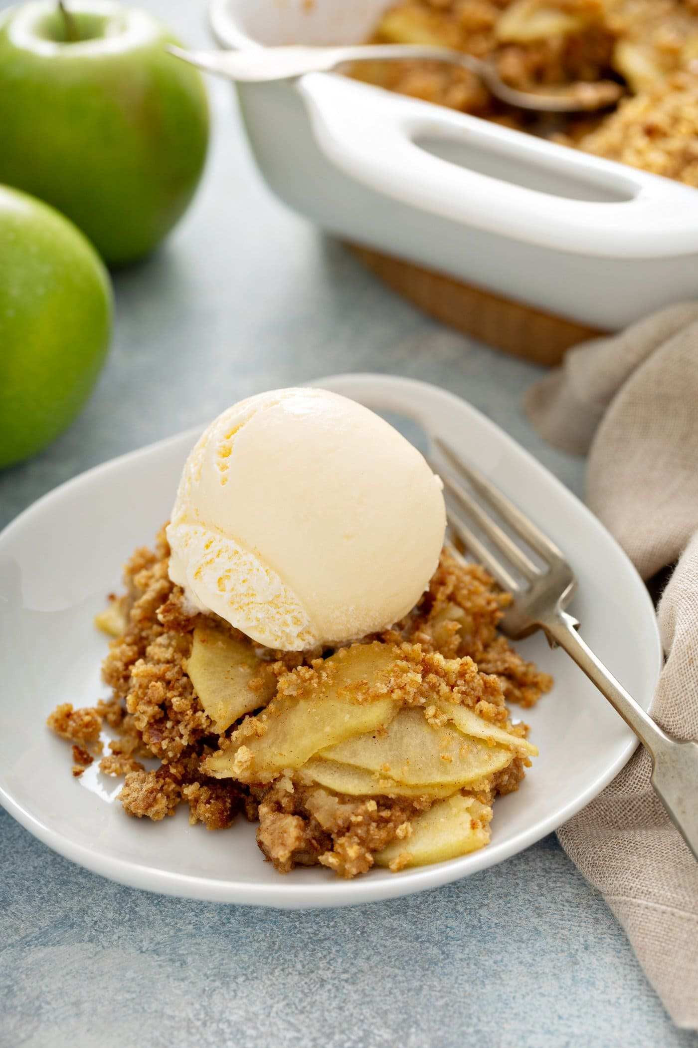 Apple brown Betty in a dessert dish. There are sliced apples with a brown bread crumb topping. The desssert is topped with a scoop of vanilla ice cream. A fork is on the plate next to the apple brown Betty. Apples, a baking dish with the dessert, and a linen napkin are behind the dessert plate.