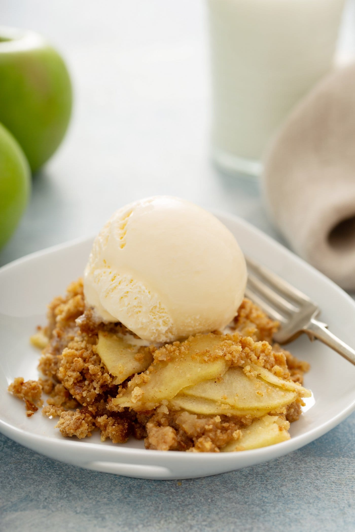 Apple Brown Betty on a dessert plate. There are slices of apples, with a brown bread crumb topping. The dessert has one scoop of vanilla ice cream on top and a fork next to it on the plate. Some green apples are in the background.