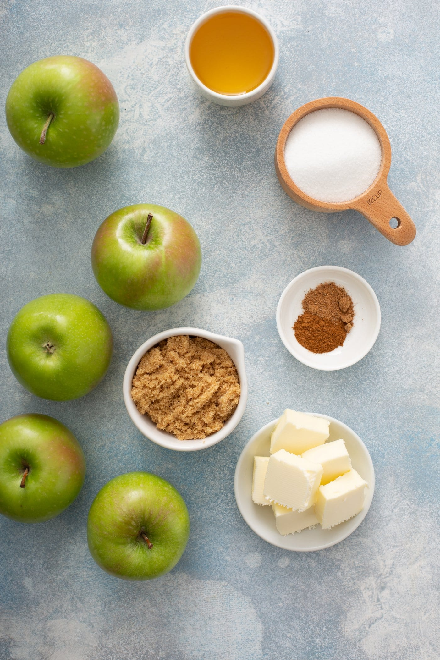 5 green apples, and containers of cubed butter, cinnamon, bread crumbs, and sugar.