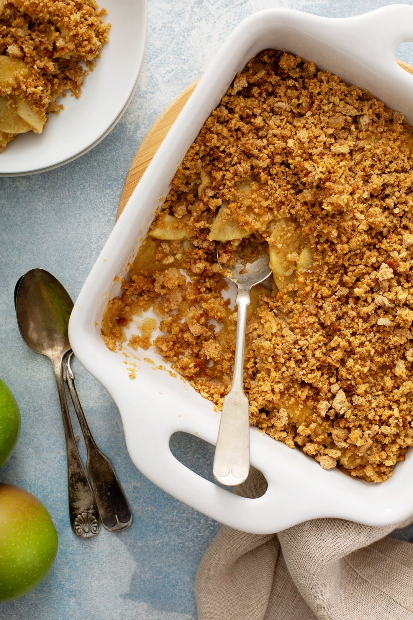 A white baking dish filled with sliced apples and topped with brown bread crumbs. There is a serving spoon in the dish and spoons and dessert dishes filled with apple brown betty in the background.