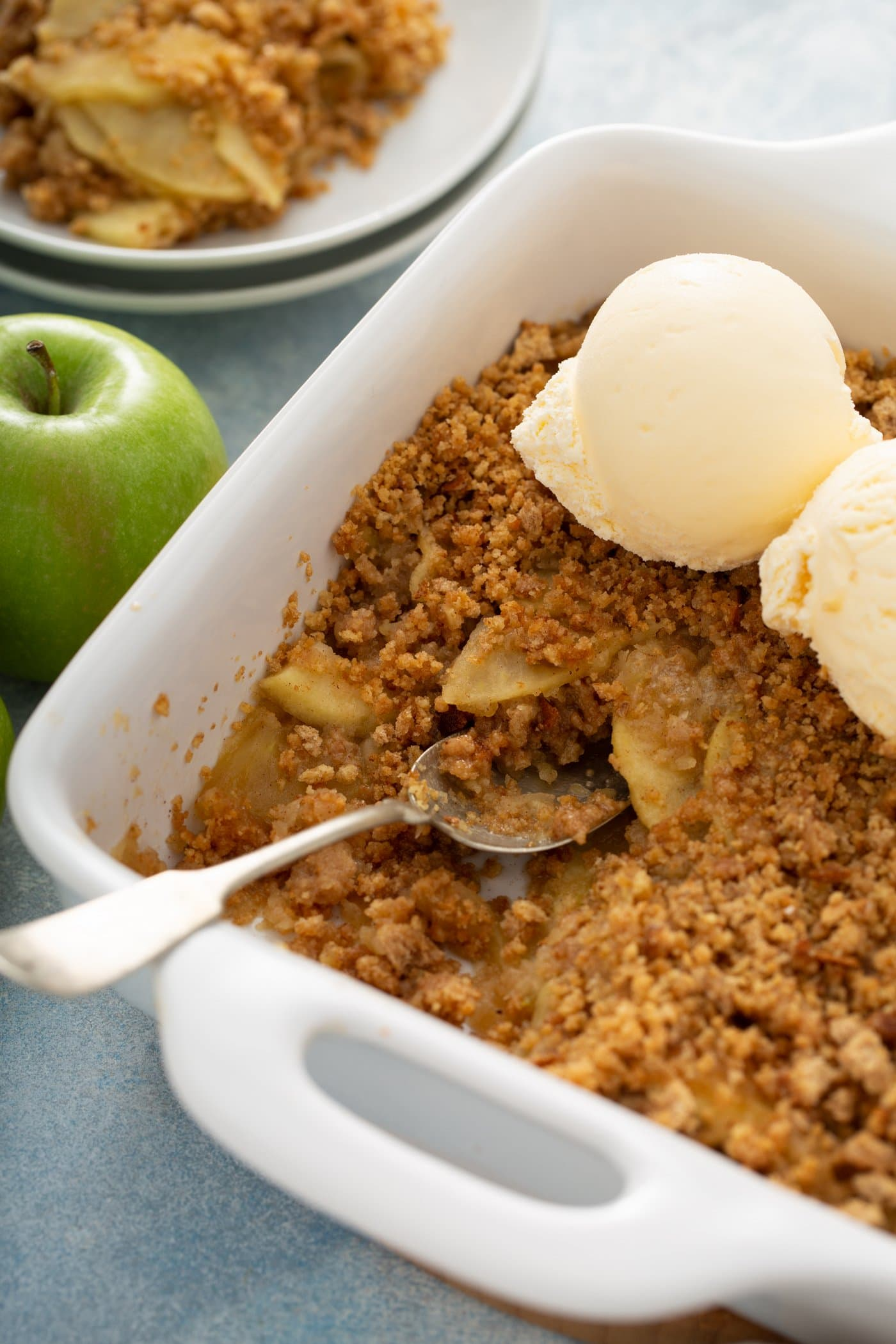 A white baking dish filled with apple brown betty. A serving spoon is in the dish and there are two scoops of vanilla ice cream on top of the apple brown Betty. An apple is next to the dish and there are dessert plates in the background.