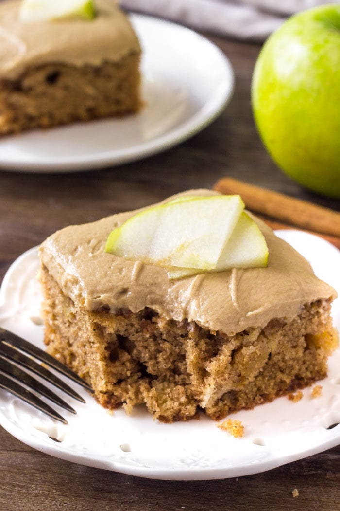 A slice of apple spice cake with caramel frosting.