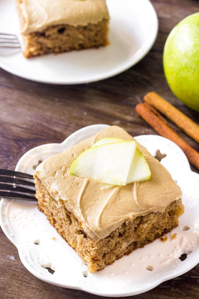 A slice of apple cake with caramel frosting topped with apple slices