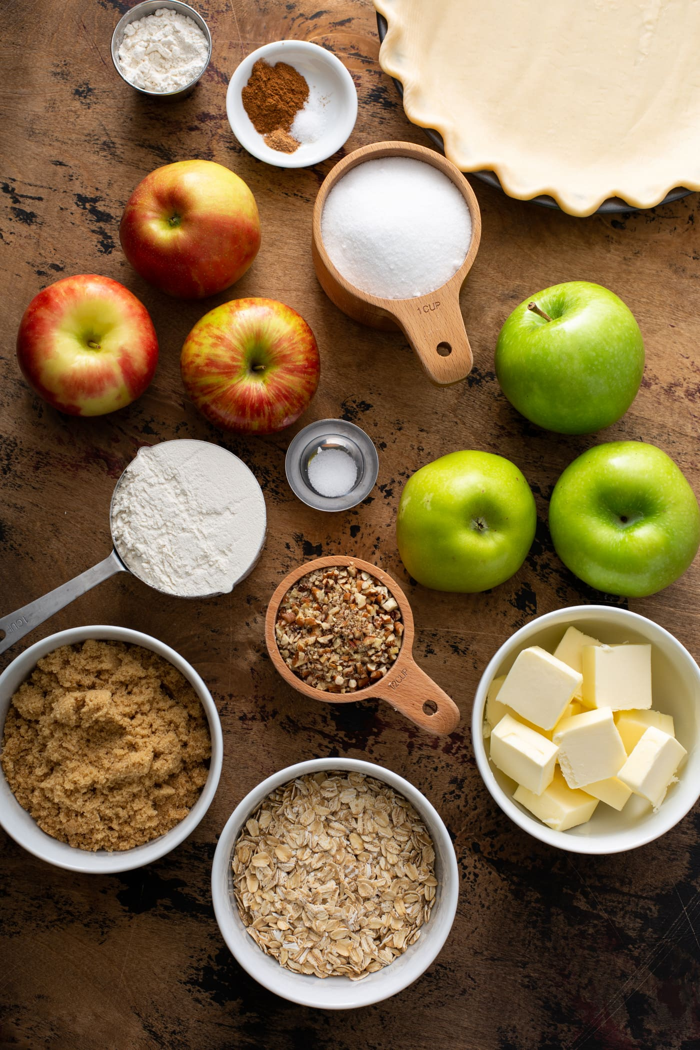 a picture of ingredients for Dutch Apple Pie. there are green apples, red apples, oatmeal, butter, sugar, brown sugar, and spices.