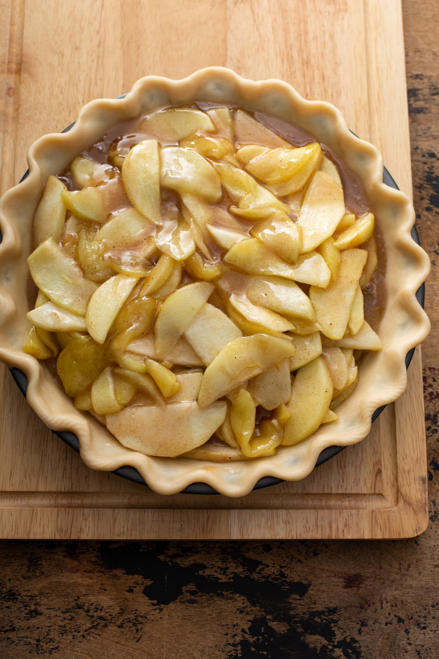 Sliced apples with melted butter and brown sugar and spices in a pastry shell.