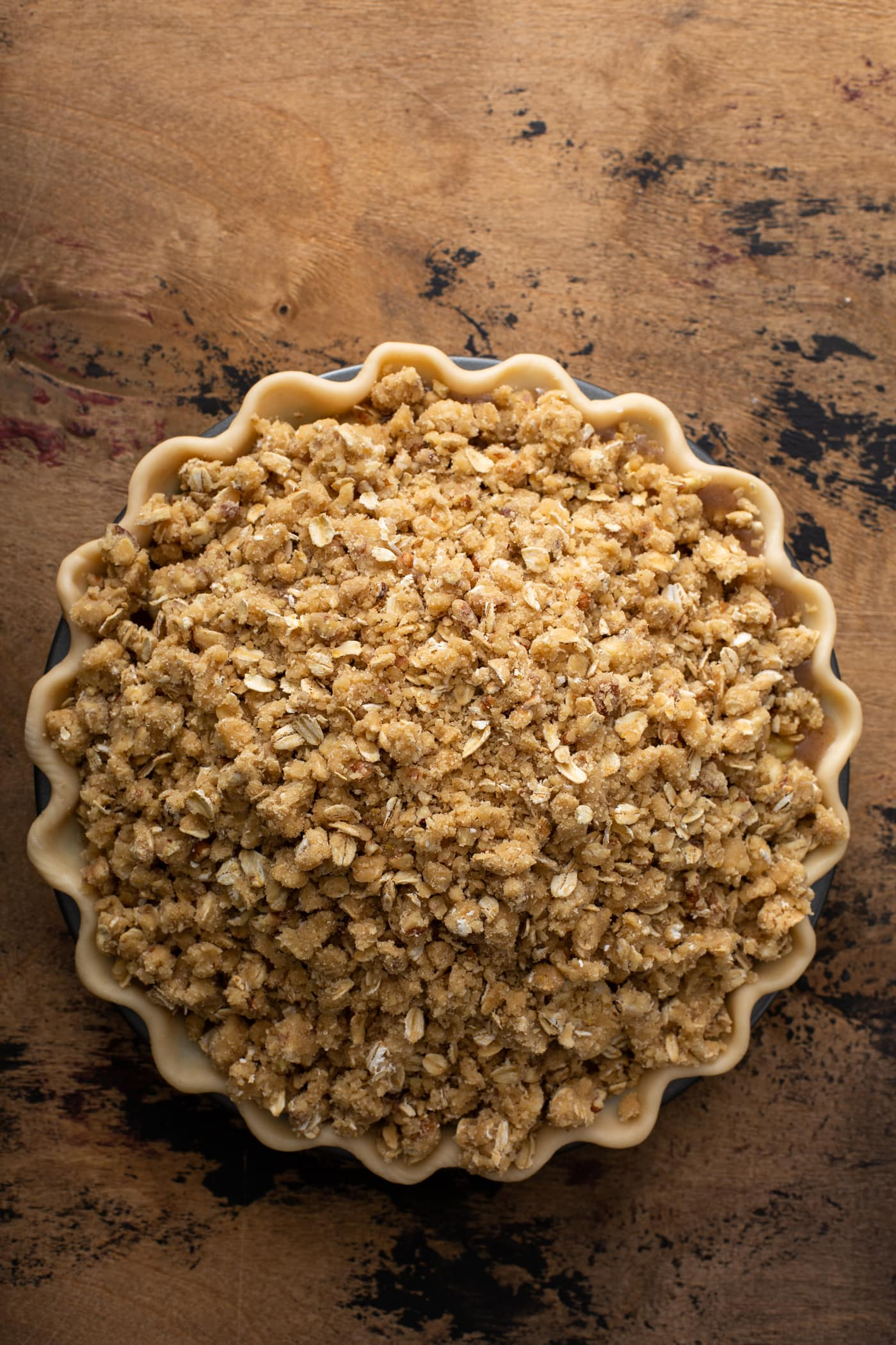 A picture of a Dutch Apple Pie ready to go into the oven. The top is covered with a nutty crumble.