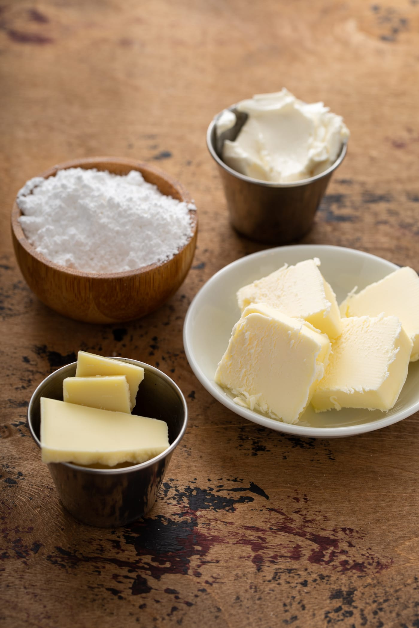 Containers of slices of butter, powdered sugar, cream cheese and white chocolate.