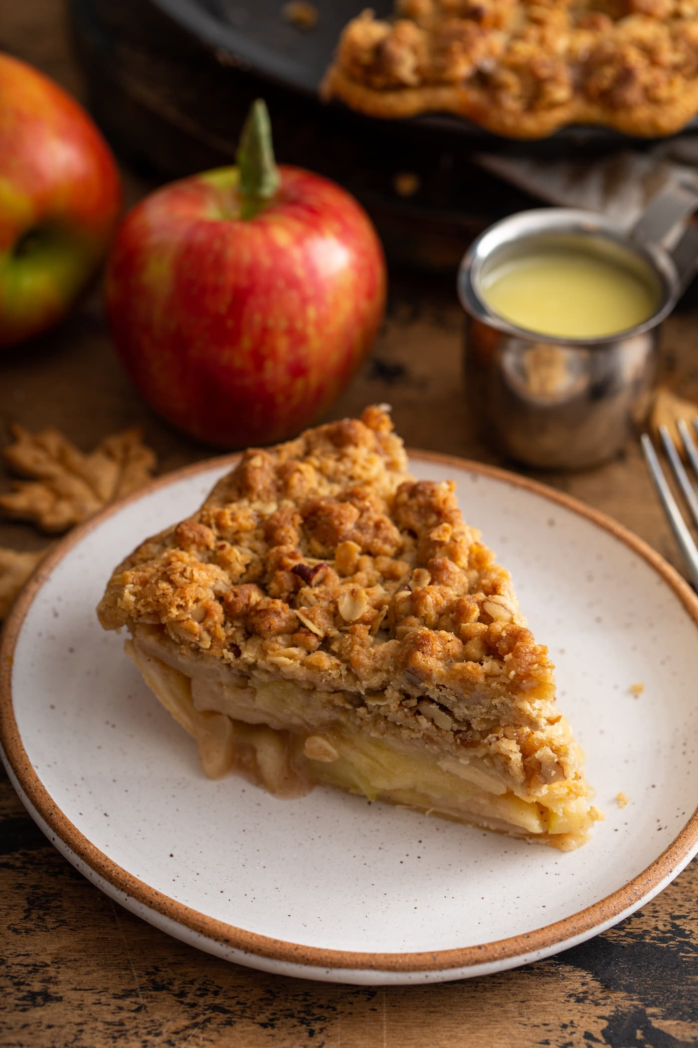 A slice of Dutch Apple Pie. You can see the apples and they are topped with a golden brown crumble. An apple and a container of sauce are in the background.