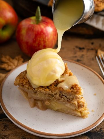 A slice of Dutch apple pie with a scoop of ice cream on top. White chocolate butter sauce is being poured over the top of the ice cream. A red apple is in the background.