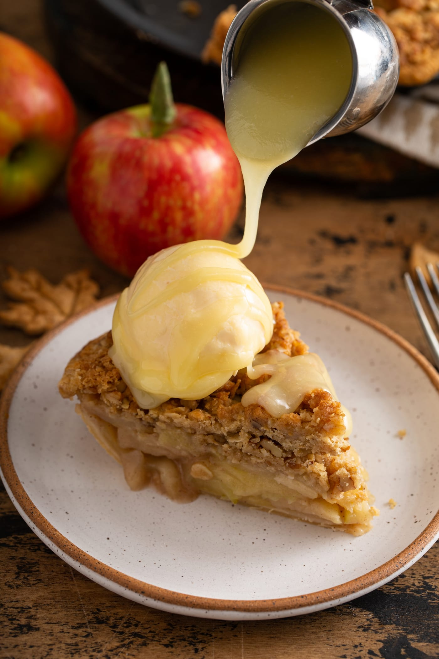 A slice of Dutch apple pie with a scoop of ice cream on top. White chocolate cheese sauce is being poured over the top of the ice cream. A red apple is in the background.