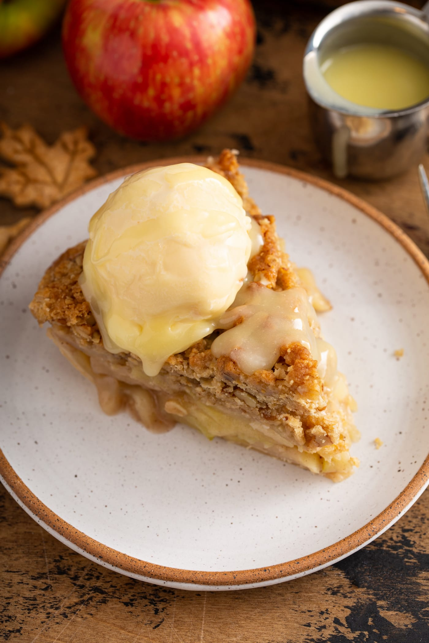 A slice of Dutch apple pie with a scoop of ice cream on top. White chocolate butter sauce has been poured over the top of the ice cream.
