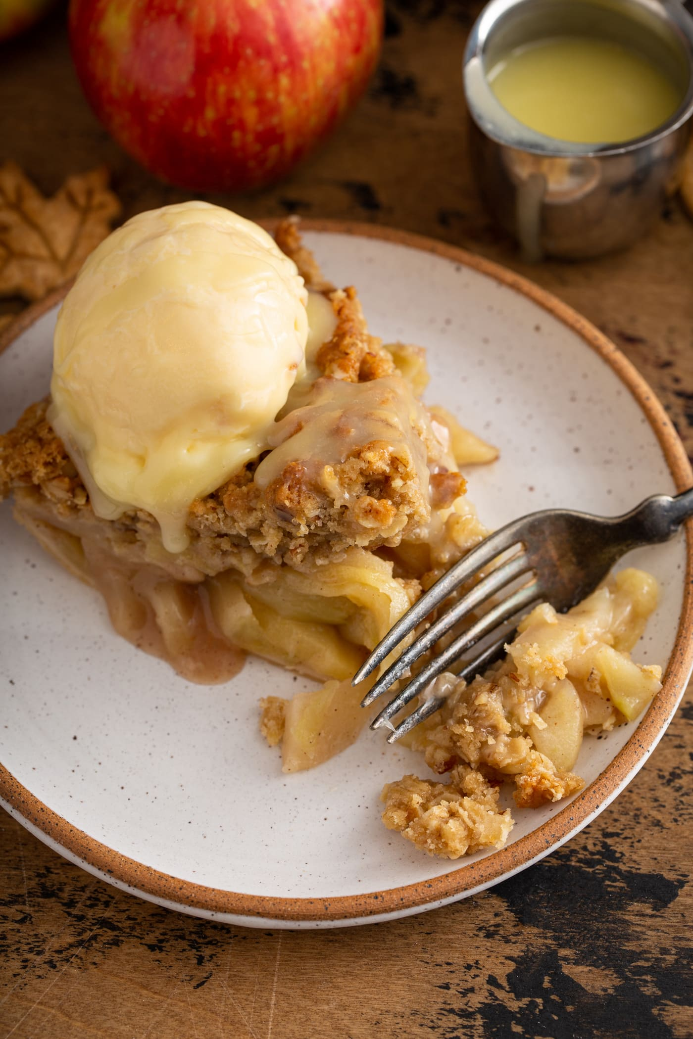 A slice of Dutch apple pie on a white dessert plate. The pie has a scoop of ice cream on top and white chocolate butter sauce is poured over all. A fork is on the plate.