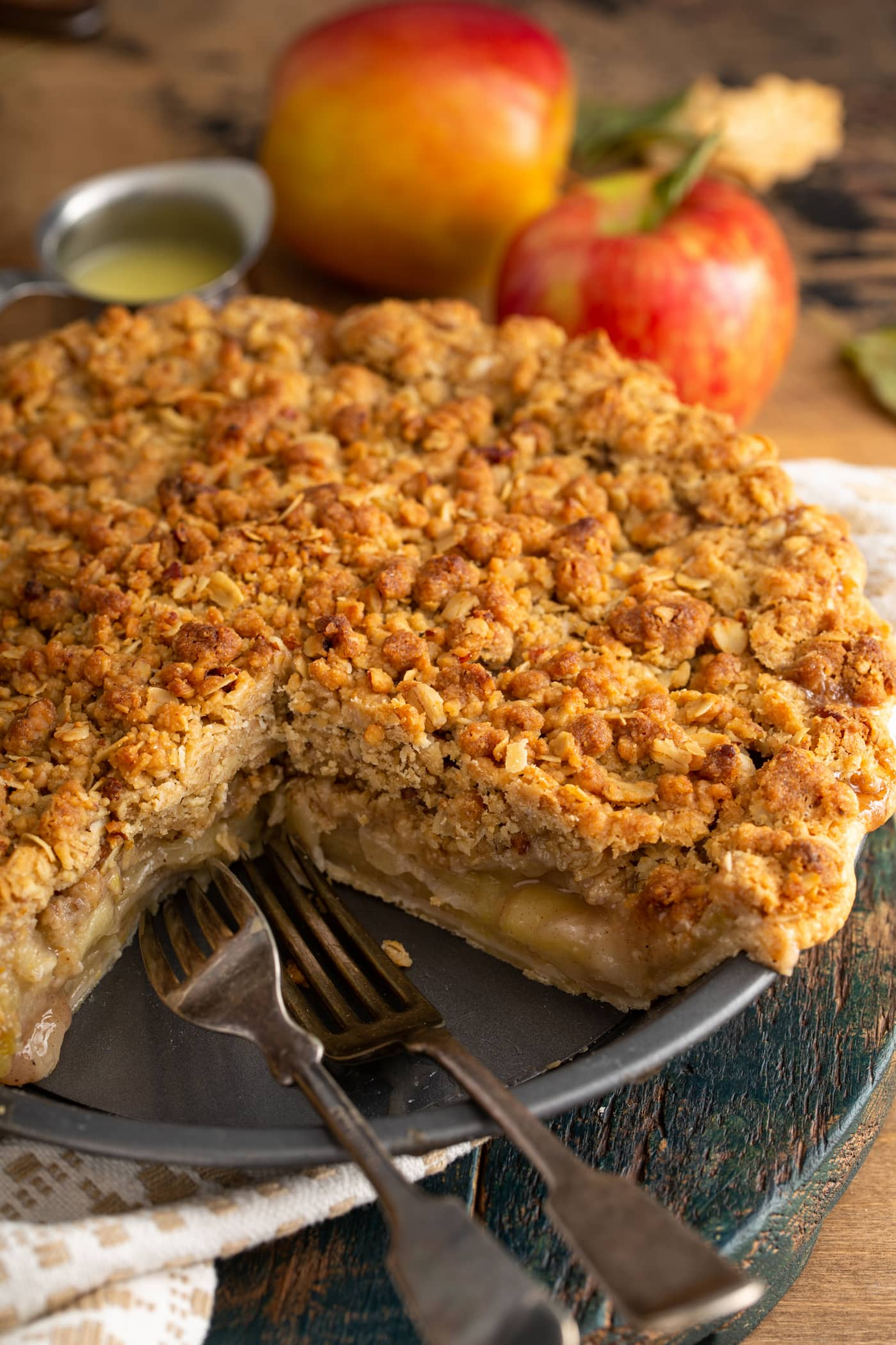 A baked Dutch apple pie with a slice removed. You can see the sliced apples inside and the brown crumble on top of the pie. A couple of apples are in the background.