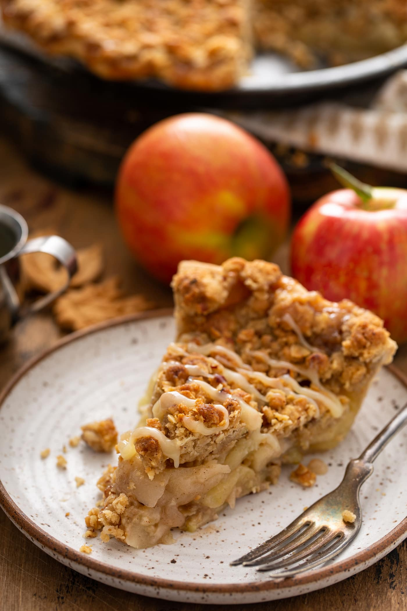 A slice of Dutch apple pie with a drizzle of white chocolate butter sauce over the top. Two apples are in the background.,
