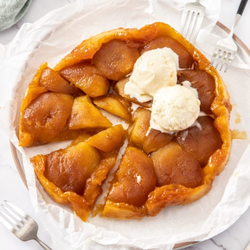 An apple tarte tatin on a sheet of baking paper on a marble surface with ice cream on top