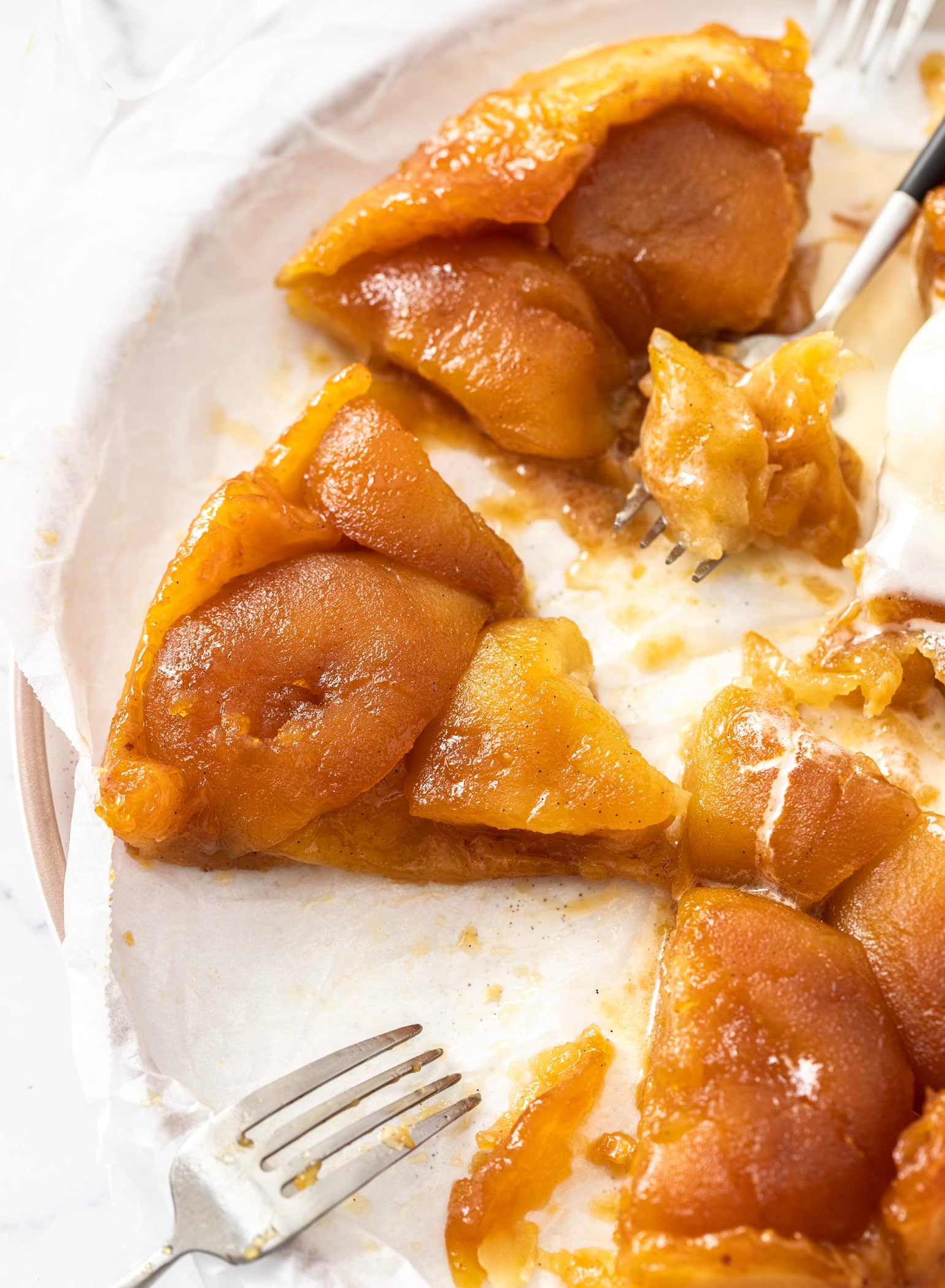 Closeup of a slice of apple tarte tatin with two forks