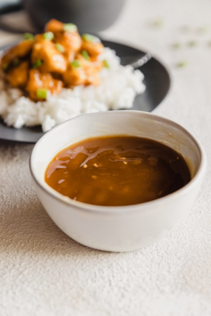 a white bowl with easy asian orange sauce for chicken and a grey plate with white long grain rice topped with orange chicken and green onions in the background