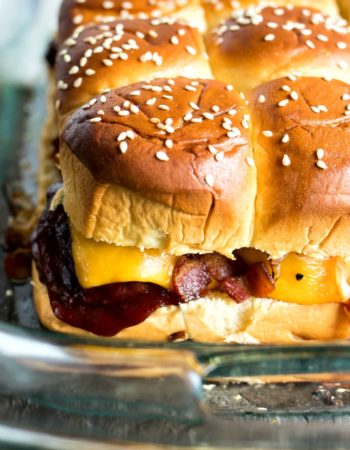 BBQ Meatball Sliders - Meatballs are tossed in sweet BBQ sauce, topped with cheddar cheese, sauteed onions, and crispy bacon and then sandwiched between sweet Hawaiian rolls. The perfect snack for all your parties and tailgates!