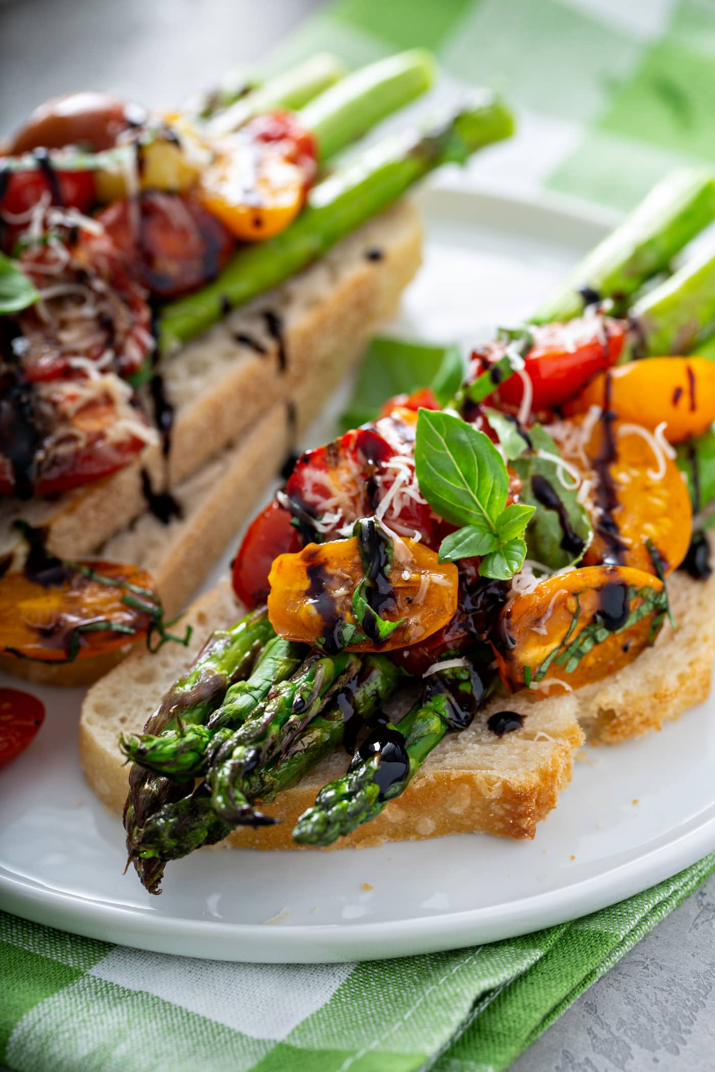 A serving of balsamic glazed roasted tomatoes and asparagus on a slice of bread. the roasted tomatoes and asparagus are drizzled with balsamic glaze and sprinkled with grated Parmesan cheese. There is another serving on two slices of bread in the background.