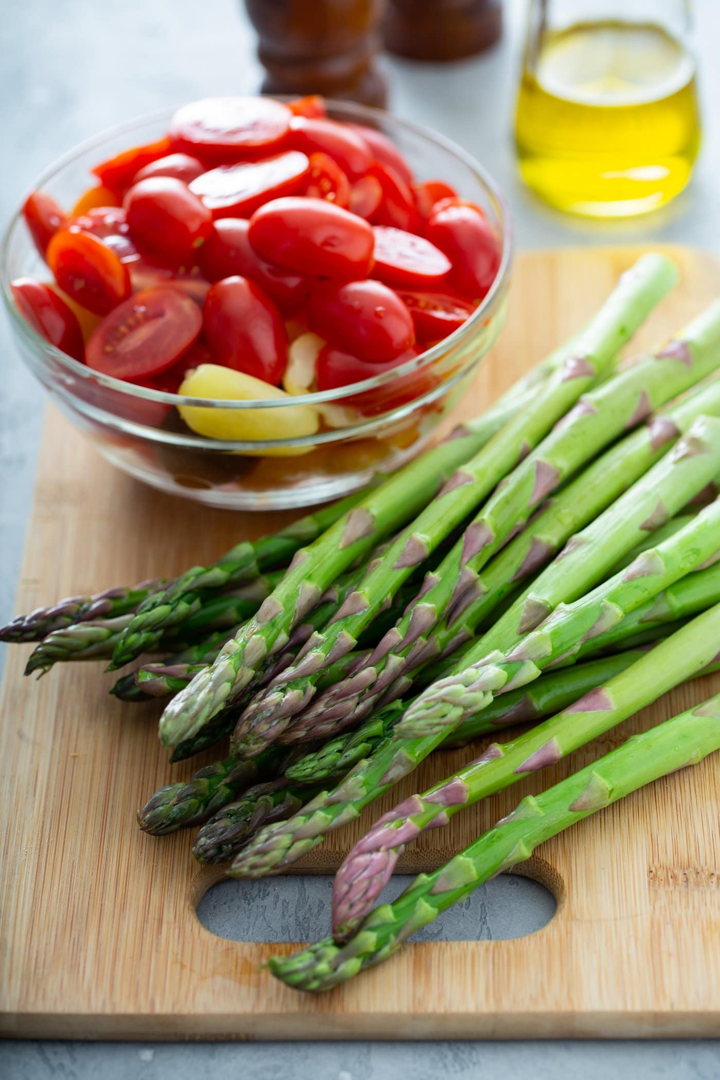 A bunch of fresh asparagus on a wood cutting board. There is a glass bowl of sliced red and yellow heirloom tomatoes next to the asparagus. A glass container of oil is in the background.