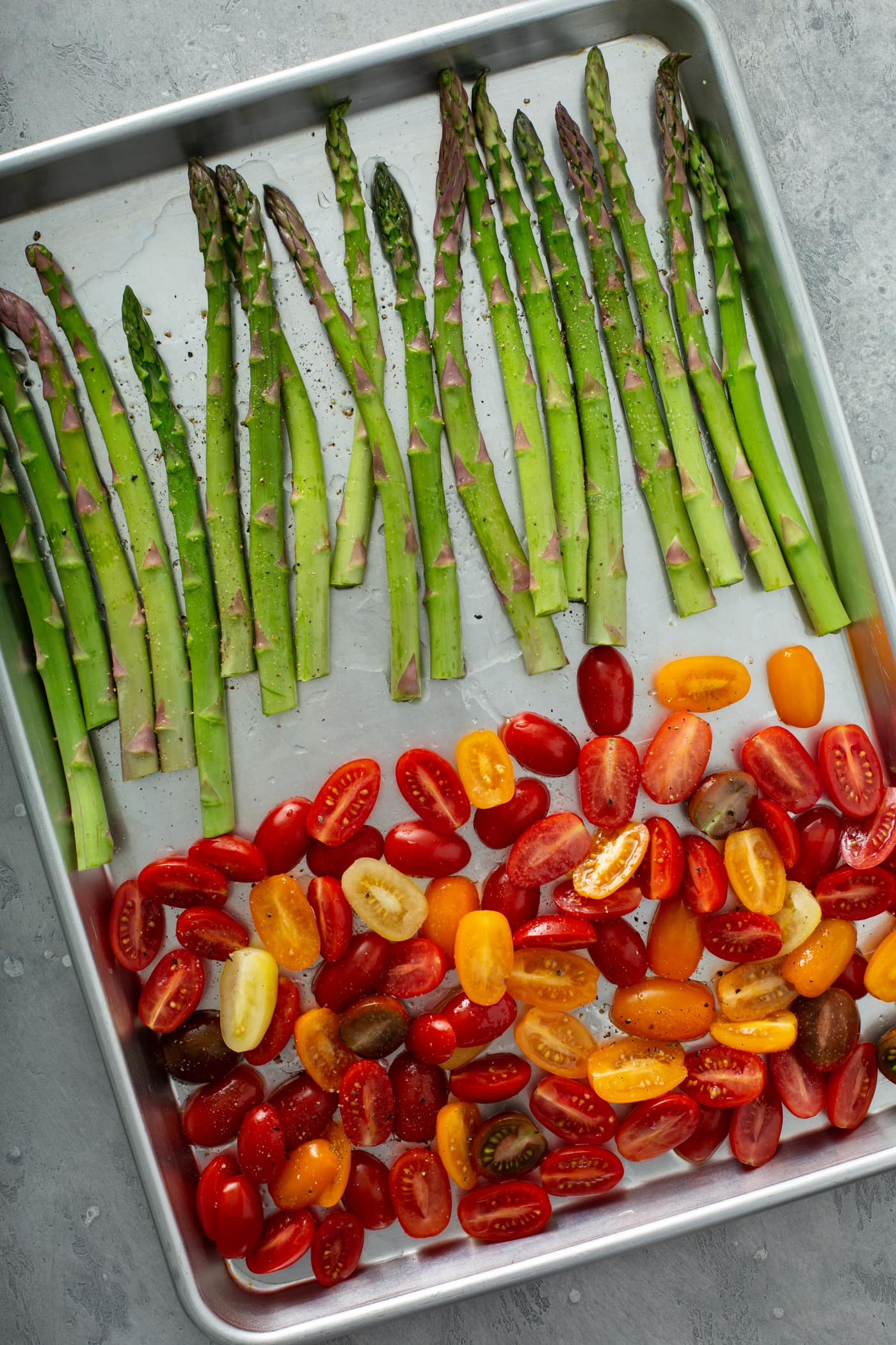 A baking pan with fresh green asparagus on one end and sliced red and yellow heirloom tomatoes on the other end.