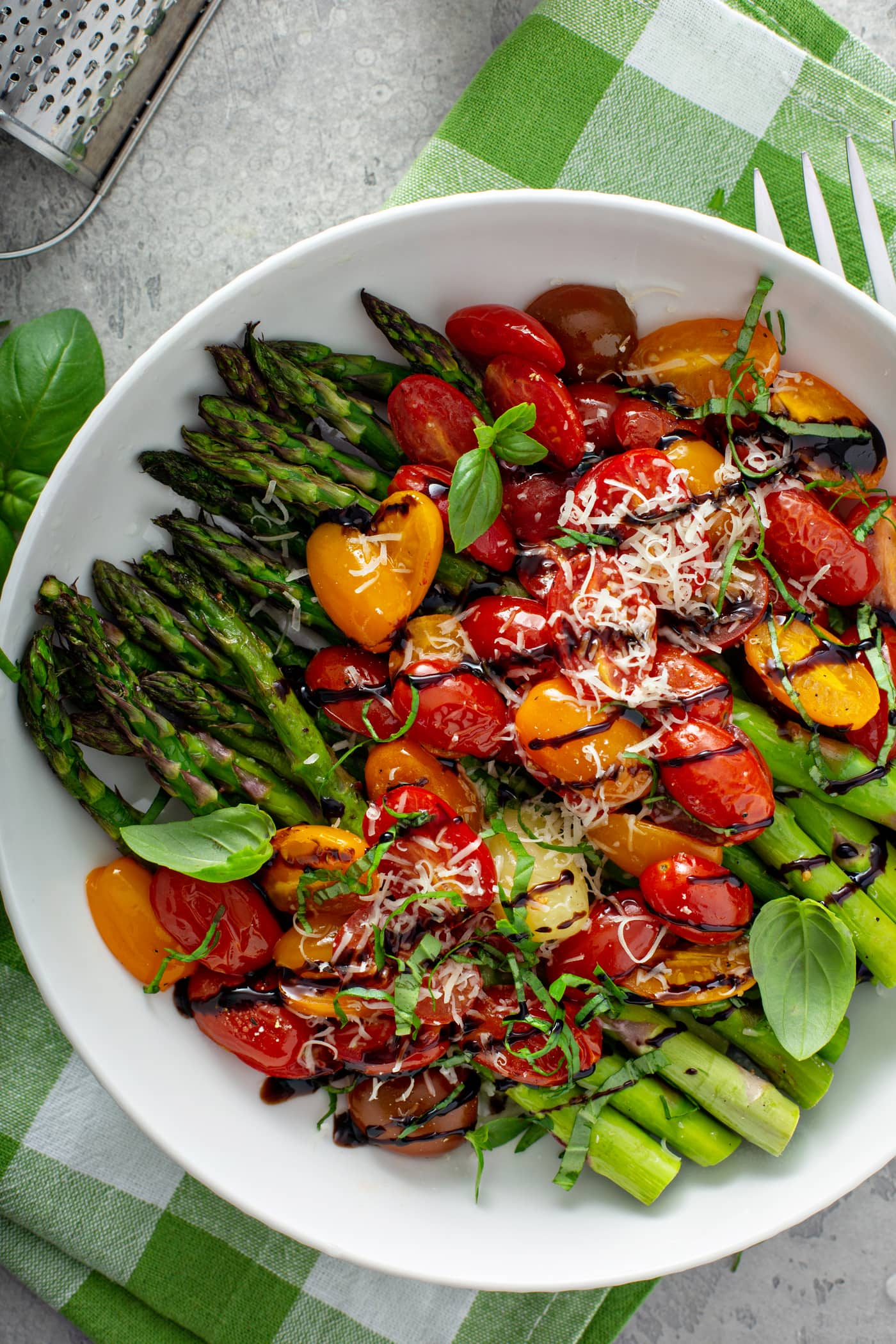 A serving dish with balsamic glazed roasted tomatoes and asparagus. The green roasted asparagus is covered with sliced red and yellow tomatoes with a drizzle of balsamic glaze over the top. Grated Parmesan cheese is sprinkled over it all. The serving dish is sitting on a green and white checked cloth.