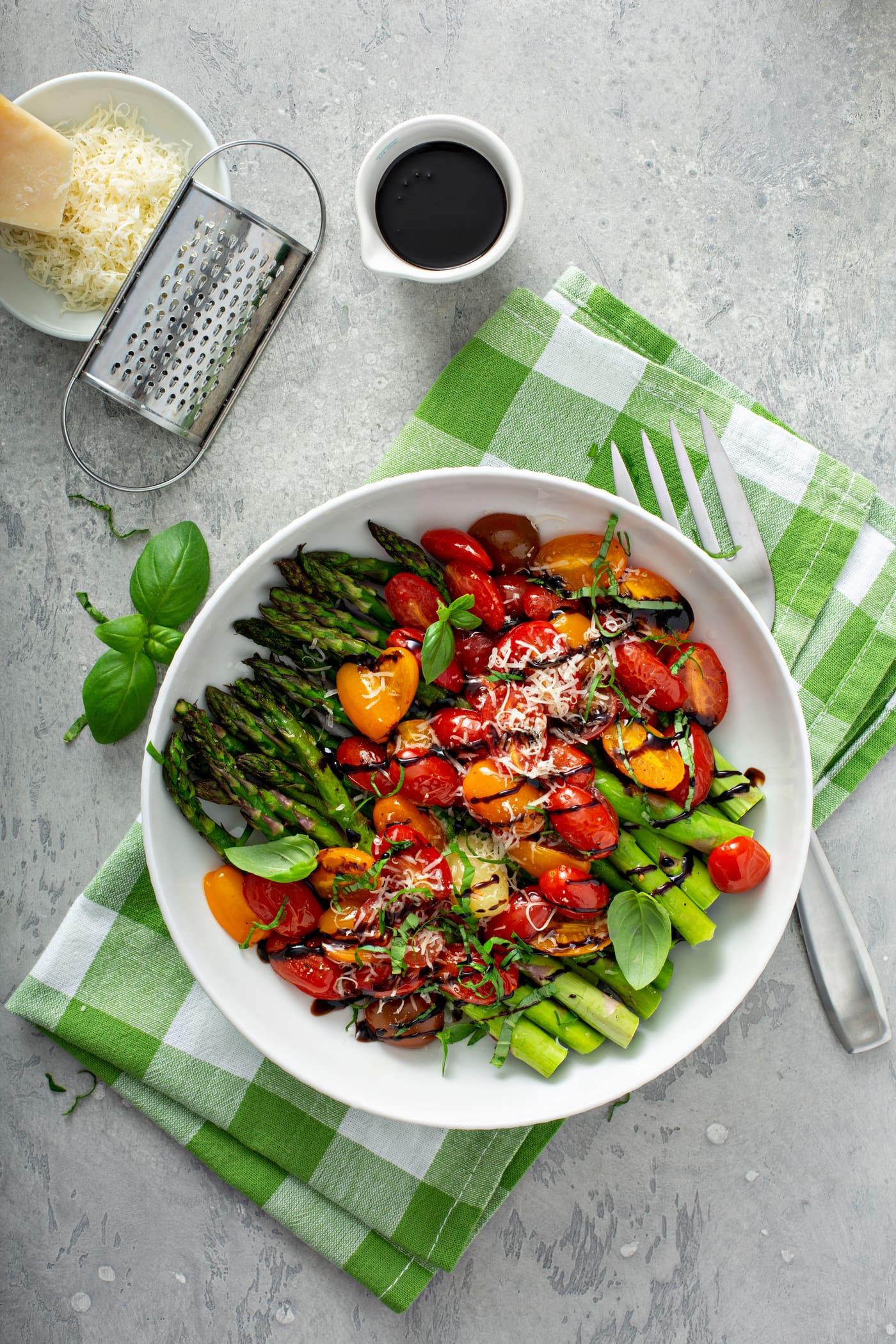 A serving dish of balsamic glazed tomatoes and asparagus. The bright green asparagus and sliced red and yellow heirloom tomatoes are drizzled with balsamic glaze and sprinkled with grated Parmesan cheese. The serving dish is sitting on a green and white checked cloth. There is a fork beside the dish and a cup of balsamic glaze and a dish of grated cheese and a cheese grater in the background.