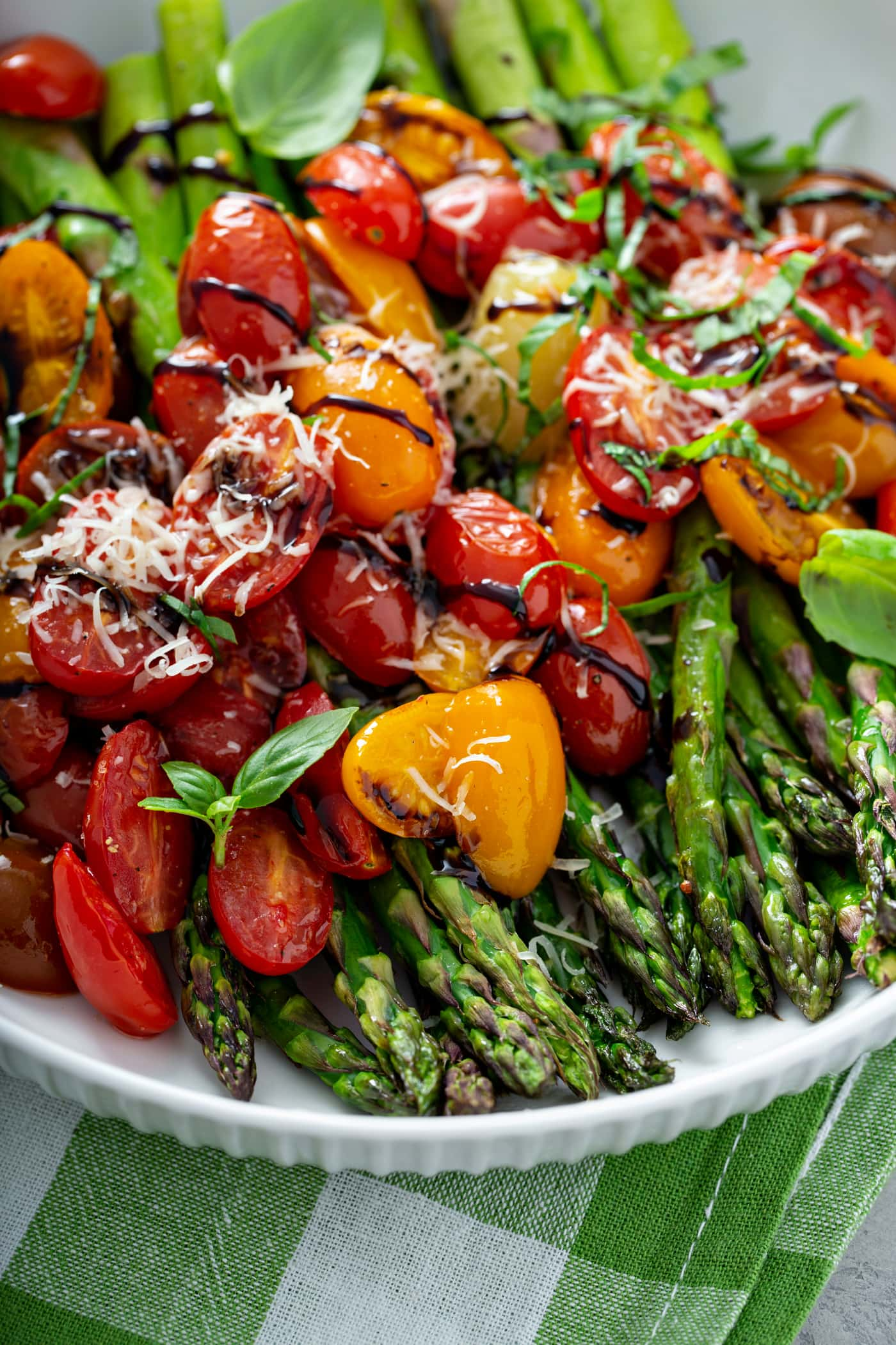 Balsamic glazed roasted tomatoes and asparagus. The bright green asparagus is topped with sliced red and yellow tomatoes and drizzled with balsamic glaze. There is grated Parmesan cheese sprinkled on top.