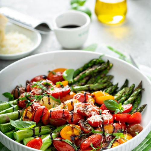 A serving dish with balsamic glazed roasted tomatoes and asparagus. The bright green asparagus and sliced red and yellow tomatoes are drizzled with balsamic glaze and topped with grated Parmesan cheese. The is a bowl of grated cheese and a brick of Parmesan cheese, a cup of balsamic glaze, and a glass container of oil in the background.