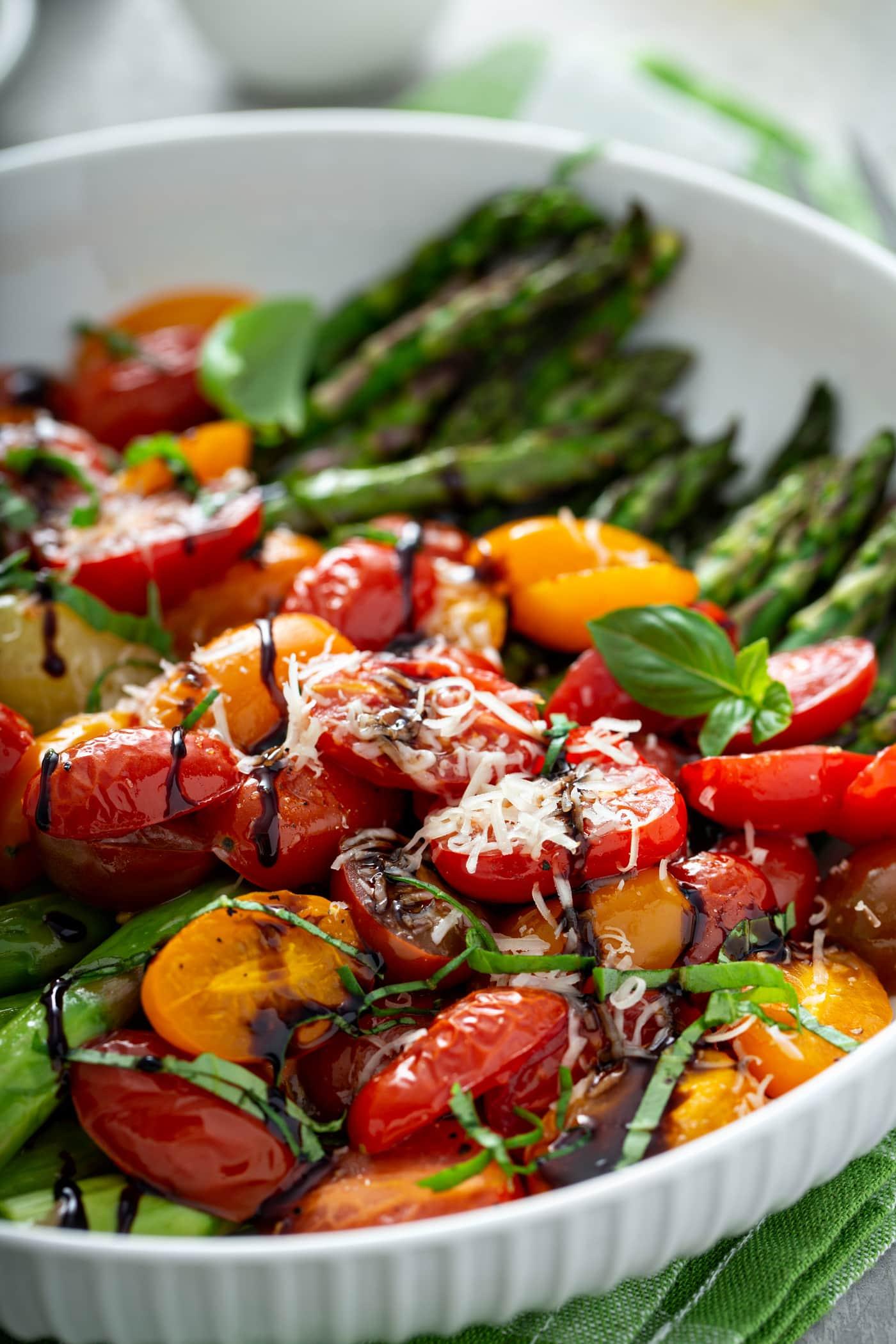 A close-up picture of balsamic glazed roasted tomatoes and asparagus. The bright green asparagus and sliced red and yellow tomatoes are drizzled with balsamic glaze and topped with grated Parmesan cheese.