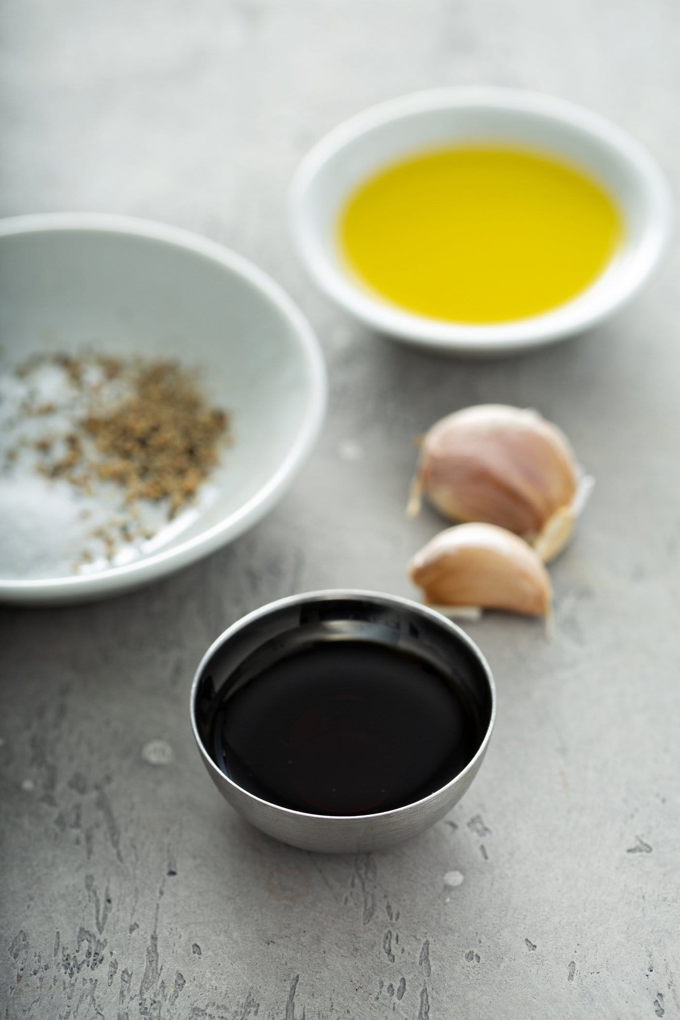 Small containers of spices, balsamic vinegar, oil and two cloves of garlic.