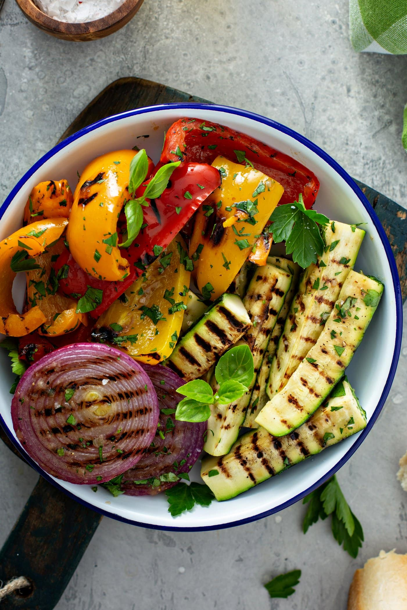 A serving dish of grilled veggies. The red onion slices, zucchini wedges and sliced red and yellow bell peppers have light brown grill marks and the veggies are sprinkled with parsley leaves.