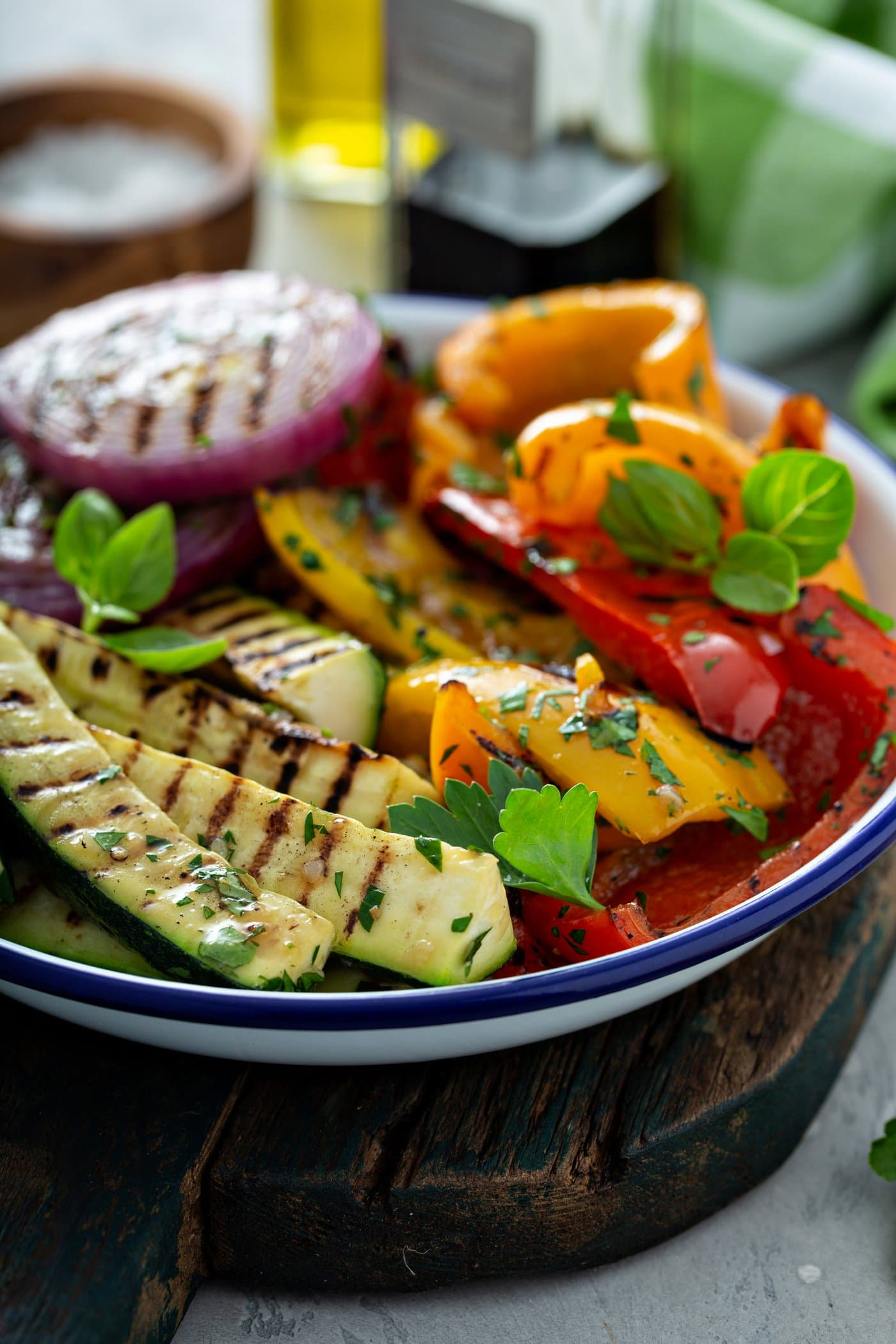 A serving dish of grilled zucchini, red and yellow bell peppers and red onions. There are golden grill marks on the vegetables and parsley leaves sprinkled on top.