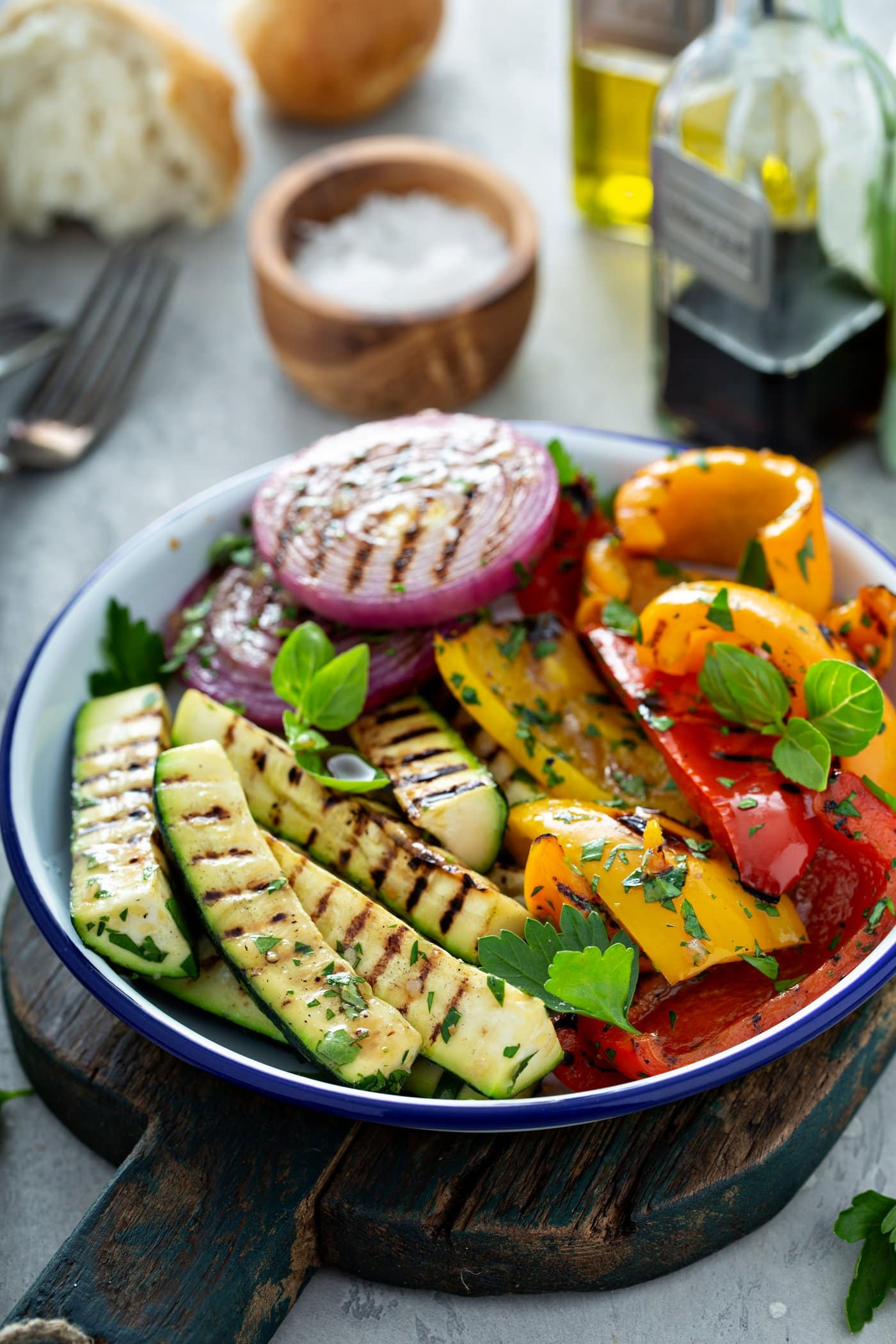 A plate of grilled vegetables. The zucchini, bell peppers, and red onions have beautiful grill marks and a few parsley leaves are scattered on top. There is a small wooden bowl of salt, a fork, and a glass cup of balsamic glaze in the background.