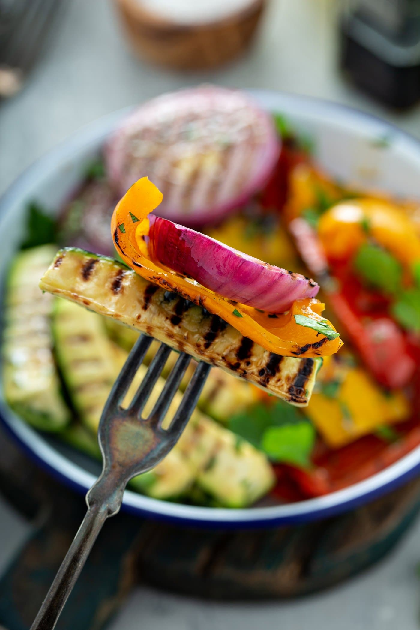 Grilled zucchini, yellow bell pepper, and red onion pierced with a fork. A serving dish of grilled veggies is in the background.