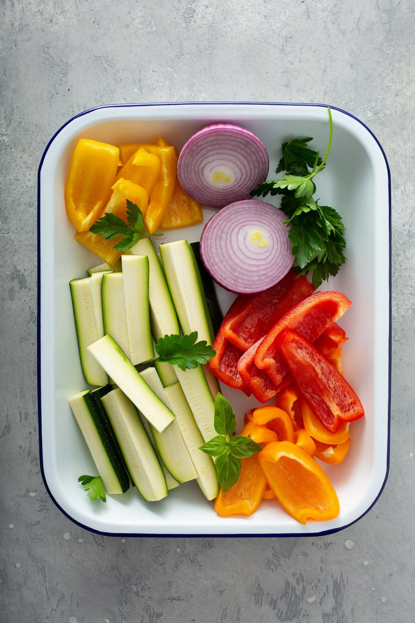 A plate with fresh zucchini wedges, sliced red onion, slices of red and yellow bell peppers, and parsley leaves.