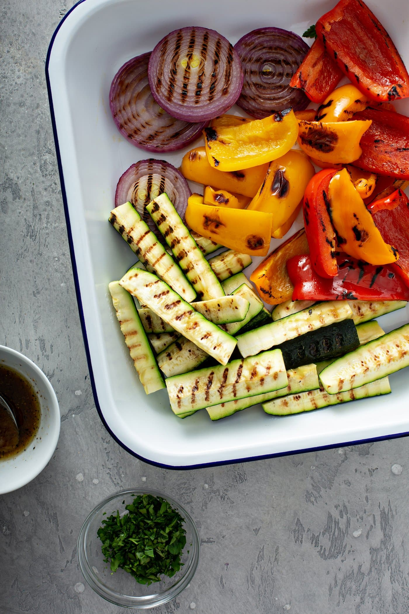A plate of grilled veggies with a cup of balsamic glaze sitting next to the plate. The grilled zucchini wedges, slices of red onion and red and yellow bell peppers have lovely grill marks on them.