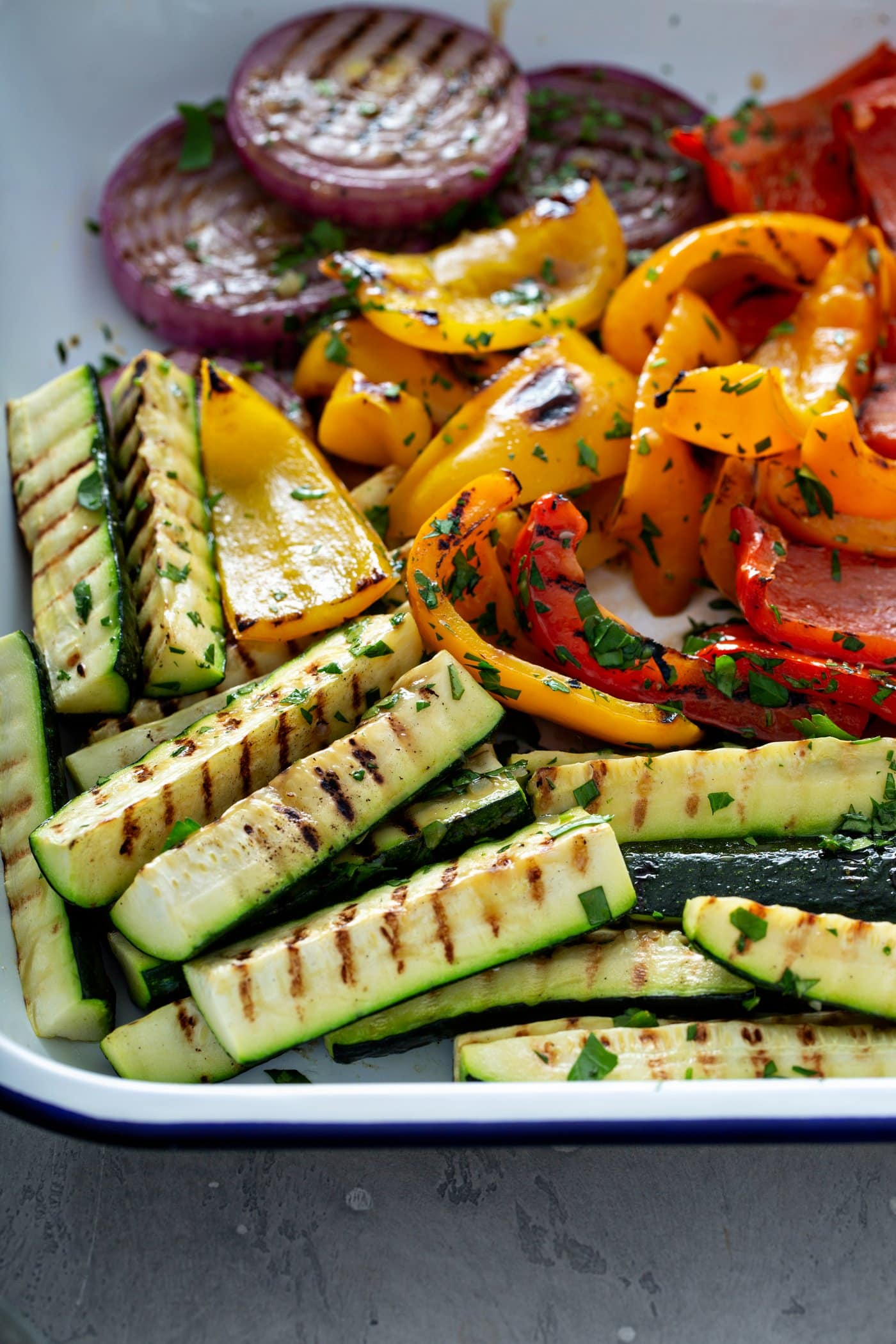 A plate full of grilled veggies. The zucchini wedges, red onion slices and red and yellow bell peppers have grill marks on them and they are sprinkled with a few parsley leaves.
