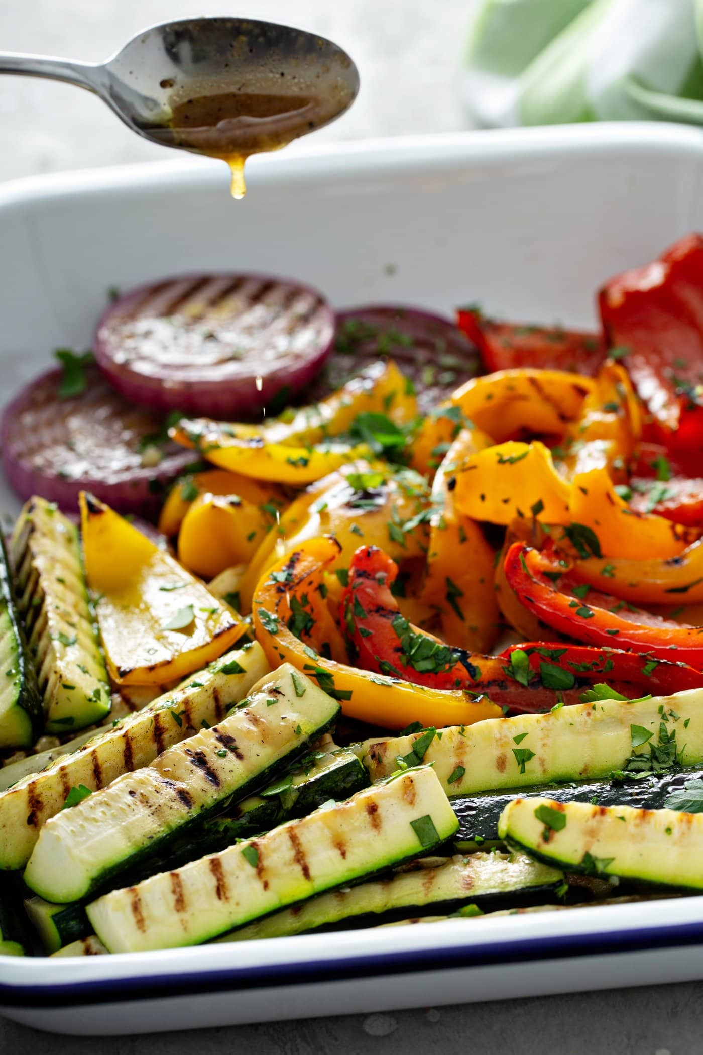 A serving dish filled with grilled veggies. The sliced red onion, zucchini wedges and red and yellow bell peppers have wonderful grill marks and there are parsley leaves scattered on top of the veggies.